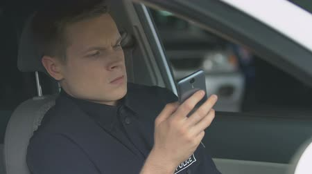 охранять : Police officer looking through websites with news on smartphone sitting in car