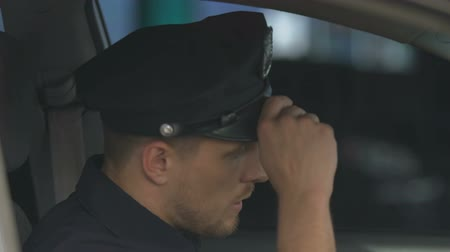 patrolman : Tired police officer getting into car and taking off service hat, hard shift