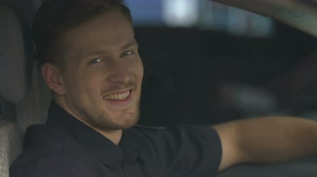patrolman : Handsome policeman sincerely smiling for camera sitting on driver seat in car Stock Footage
