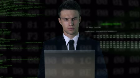 hacker computer : Man in suit typing on laptop, software code on background, password hack Stock Footage
