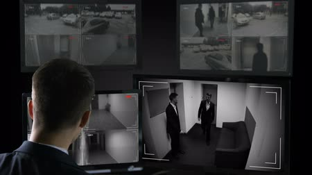 witness : Male security operator watching surveillance cameras, illegal business deal Stock Footage