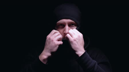 villain : Serious man putting on balaclava, preparing for murder or robbery, banditry