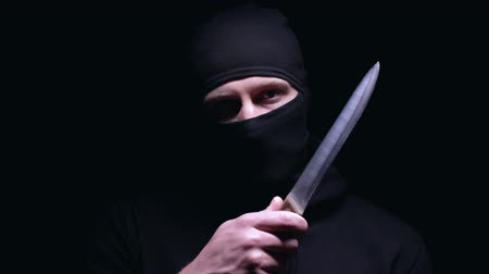 villain : Insane murderer touching his masked face with big knife, threatening with murder