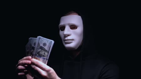 villain : Fearful man in face mask looking at dollars in his hands, robbery, cyber attack Stock Footage