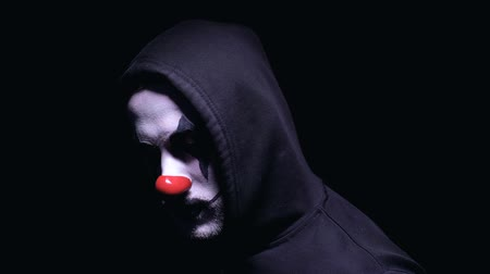 убивать : Fearful clown man appearing from darkness and smiling, terrible nightmare