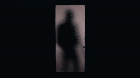 гангстер : Dark shadow of hooded man coming and opening glass door, danger of burglary