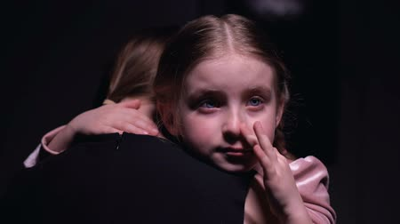 přestupek : Little crying girl wiping tears and embracing mother, bullying victim, offense