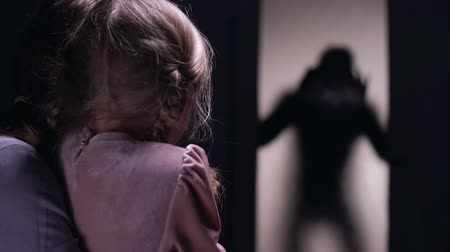maltreatment : Terrified woman and daughter hiding in room, criminal silhouette opening door Stock Footage