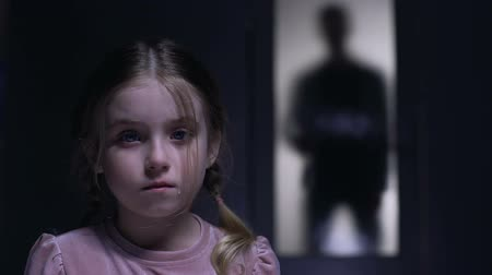 maltreatment : Crying little girl looking at camera silhouette of alcoholic father outside door, conceptual Stock Footage