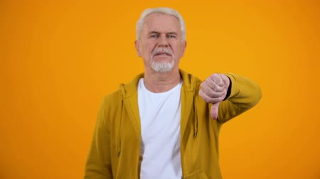 неправильно : Displeased elderly man showing thumbs-down gesture, dislike, negative feedback Стоковые видеозаписи
