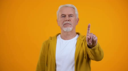 disapprove : Elderly male in casual clothes showing warning finger gesture, rejection sign