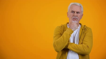decidir : Senior man touching chin, thinking about decision against orange background