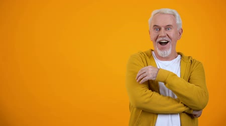 astonishment : Astonished male pensioner expressing wow gesture against orange background Stock Footage