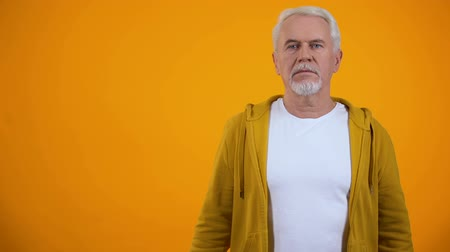 divu : Man in his 50s shocked with unexpected news against orange background, confusion Dostupné videozáznamy