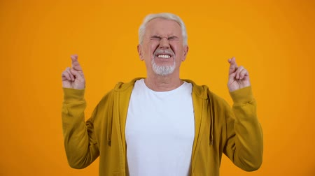 hopeful : Male in his 50s crossing fingers for luck, hoping for victory, orange background Stock Footage
