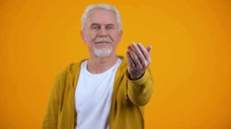 招待状 : Friendly male pensioner showing come here gesture, welcoming person, invitation
