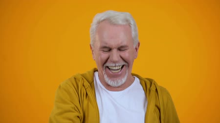 travessura : Optimistic senior man sincerely laughing against orange background, happiness
