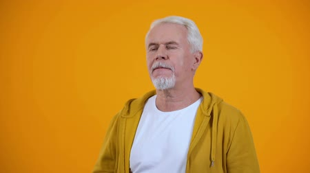 facepalm : Gray-haired pensioner showing face-palm gesture against orange background, fail Stock Footage