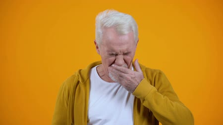 tiredness : Sleepy aged man yawning on camera against orange background, insomnia problem