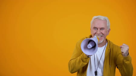 мегафон : Elderly male sport coach shouting in megaphone, sincerely supporting team, faith