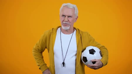 gururlu : Professional proud aged trainer with football posing on camera, sport career