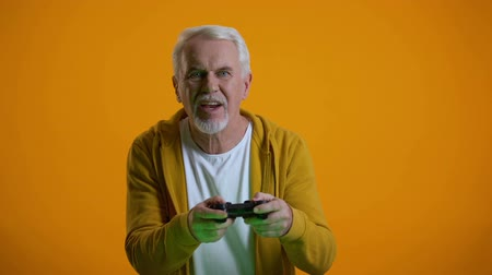 perdedor : Emotional senior man with joystick playing videogame, upset with round result
