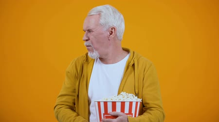 snoepen : Man in his 50s displeased with uninteresting_1080.movie, throwing popcorn at camera Stockvideo