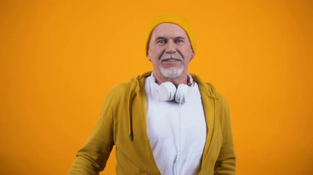 favori : Funny grandfather in headphones and casual clothes dancing to music, happy dj
