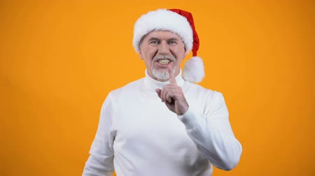 sigilo : Happy gray bearded man in santa claus hat showing silence gesture and smiling