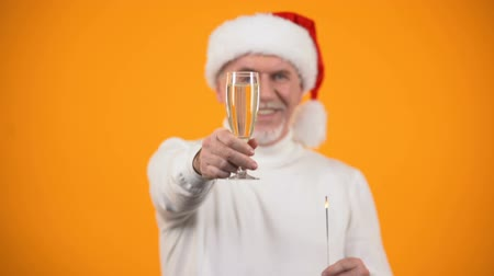 bengálsko : Glad senior man in santa claus hat with bengal light showing champagne glass Dostupné videozáznamy