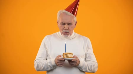 фон : Lonely senior male blowing candle on birthday cake, sadly looking at camera