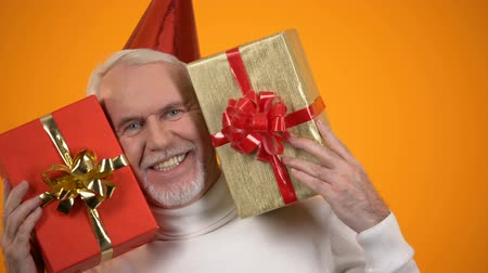 delighted : Extremely joyful retiree holding two giftboxes and smiling on camera, happiness