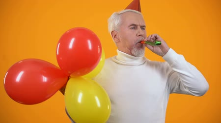 kalap : Glad male pensioner using party blower and holding colorful balloons, birthday