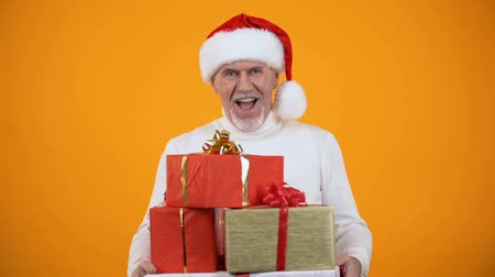 envolto : Secret senior santa presenting giftboxes and smiling on camera, holiday sale