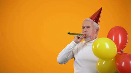 kalap : Cheerful senior man with colorful balloons using party blower, event agency
