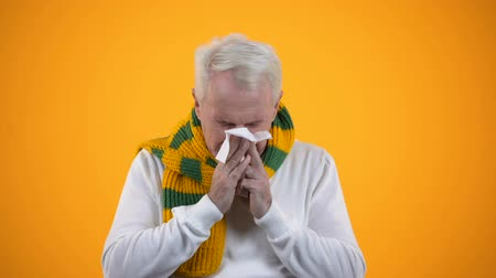 febre : Aged male in scarf blowing nose in tissue, rheum or rhinitis, influenza symptom