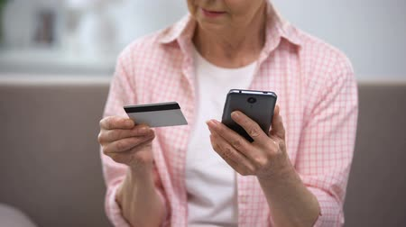 hasznosság : Senior female entering credit card number on smartphone, paying bills online Stock mozgókép