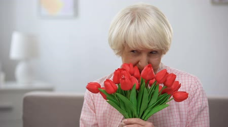 happy holidays : Happy elderly woman sniffing bunch of tulips and smiling at camera, mothers day