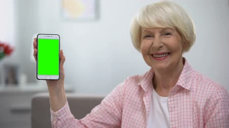 aposentar : Cheerful old woman showing smartphone with green screen at camera, application