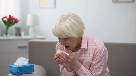 yaşlılar : Sick senior woman sneezing in tissue at home, flu virus disease, infection Stok Video