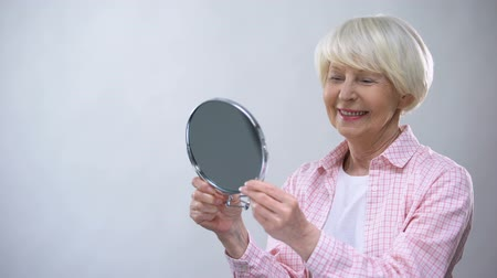 outlook : Smiling aged woman looking at mirror reflection, enjoying beauty, appearance