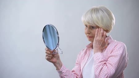 chirurgia estetica : Elderly woman looking at wrinkled face in mirror, thinking about plastic surgery Filmati Stock