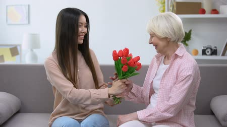 dziadkowie : Beautiful young lady presenting bouquet of flowers to grandmother, surprise