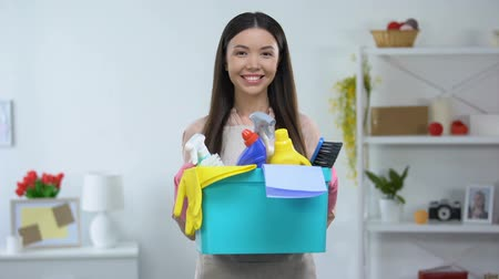 chemical agent : Smiling woman holding basket with detergents, cleaning service, housekeeping Stock Footage