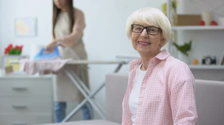 гладильный : Smiling old woman looking at camera, granddaughter ironing clothes on background