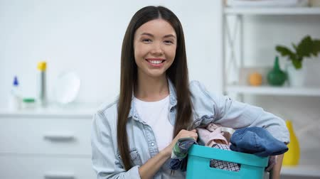 housekeeper : Young housewife holding basket with dirty clothes, looking at camera, laundry Stock Footage