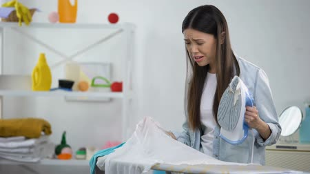 гладильный : Disappointed woman looking at hole on blouse after ironing, lack of experience