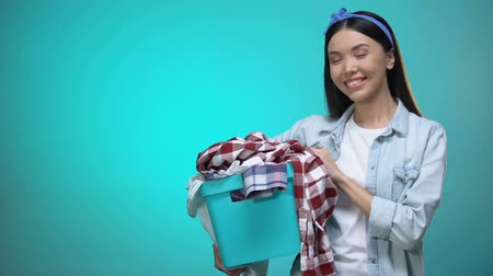 гладильный : Cheerful woman holding laundry basket and smiling at camera, template for text Стоковые видеозаписи