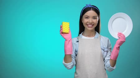 промывали : Housewife in gloves showing sponge and clean plate at camera, domestic work