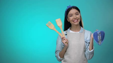 промывали : Pretty housewife in apron holding kitchenware and smiling at camera, cooking Стоковые видеозаписи